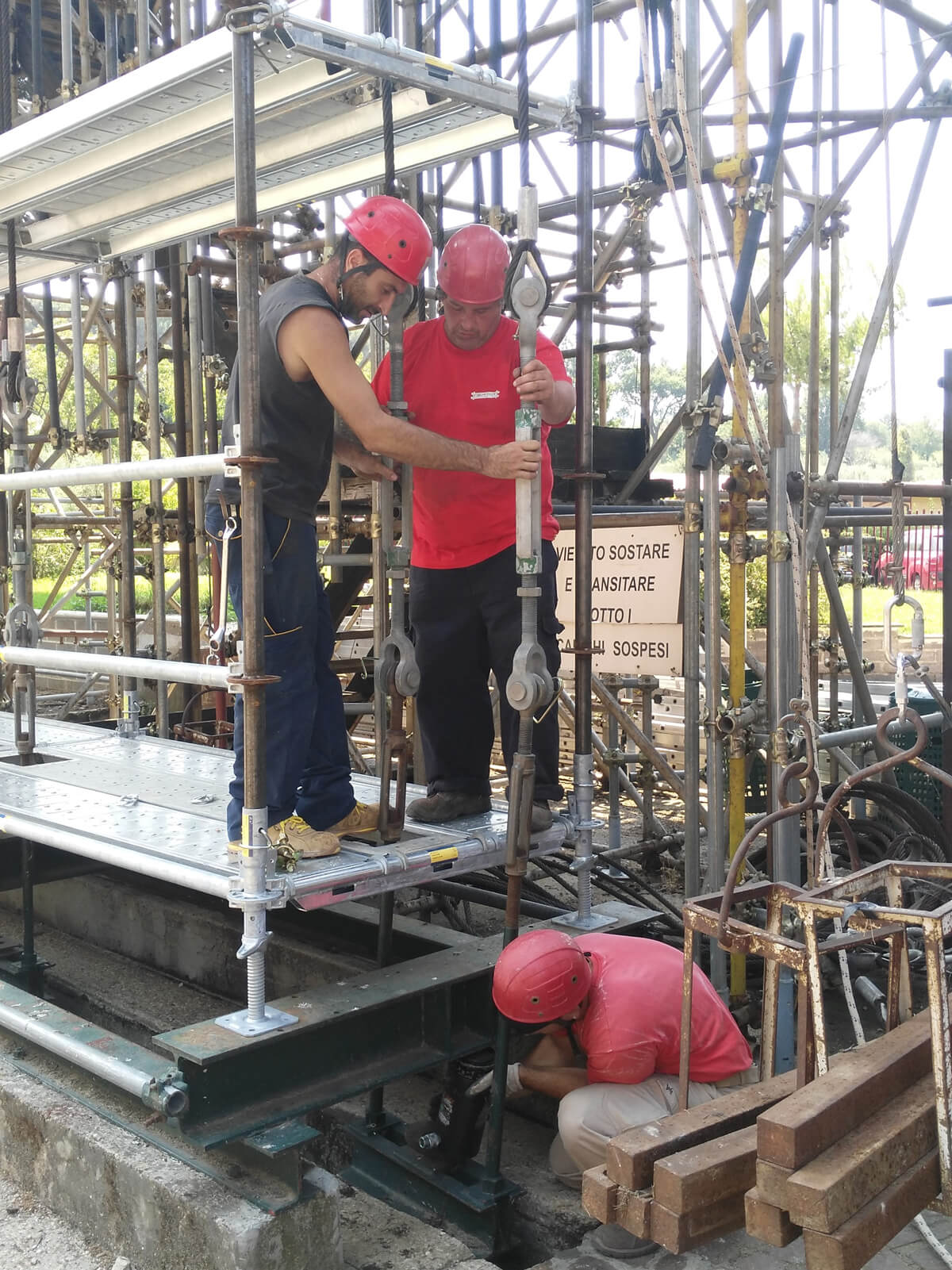 workers mounting the hydraulic piston beneath the feet of the scaffold