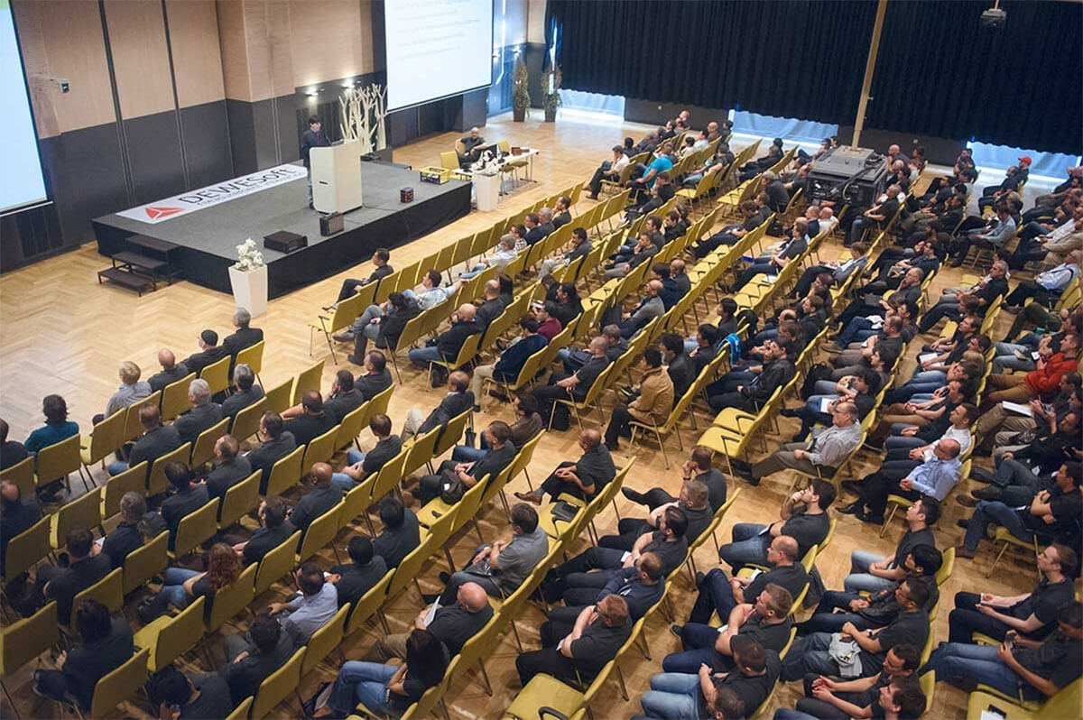 people sitting for dewesoft measurement conference in hall with stage